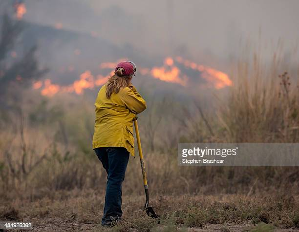 A spotter keeps and eye on a wildfire which is part of the Okanogan Complex as it burns brush on August 22 2015 near Omak Washington The fires have...