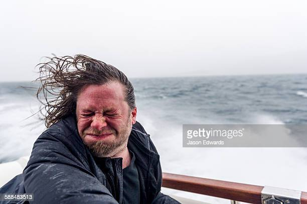 Spray and sleet lashes the face of a man on a speeding boat in a storm.