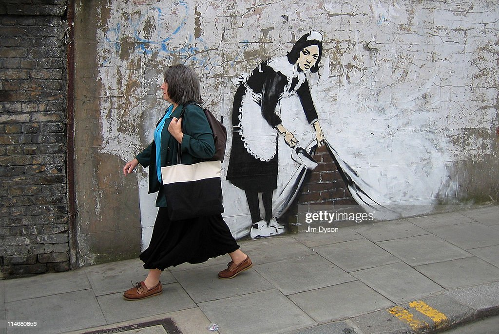 A spray and stencil artwork, attributed to guerrilla graffiti artist Banksy, appears in Camden on May 16, 2006 in London, England. The striking large scale spray-painted image entitled 'Sweeping It Under The Carpet' depicts a maid who cleaned the artist's room in a motel in Los Angeles. The piece commissioned by 'The Independent' newspaper edited on Tuesday by U2's frontman Bono, is intended to represent a metaphor for the west's reluctance to tackle issues such as Aids in Africa.