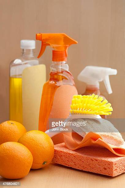 Spray bottles, sponge, scrubber and oranges