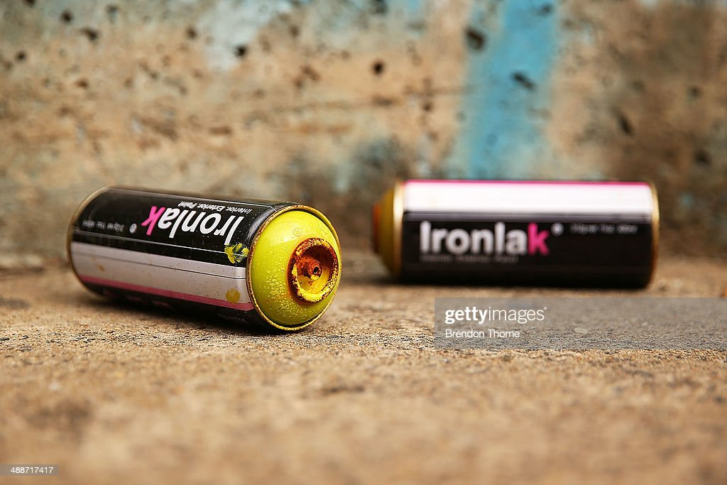 Spray cans sit next to a wall strewn with graffiti on May 8, 2014 in Sydney, Australia. The Grafitti Control Amendment Act passed in the NSW legislative council yesterday includes tougher penalties a the ability for local courts to enforce community clean up duty on offenders.