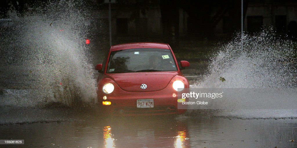 Spray flies as a car plows through a big puddle on the Fenway in Boston, Mass. from rains and wind caused by Hurricane Sandy Oct. 29, 2012.