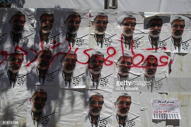 Spray paint that reads in Farsi 'only Ahmdinejad' is seen over electoral campaign posters for presidential candidate Mir Hossein Mousavi in Tehran on...