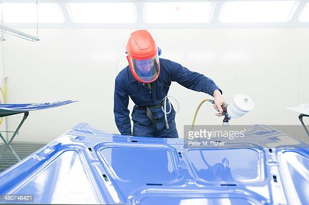 Spray painter working on car panel in spray booth
