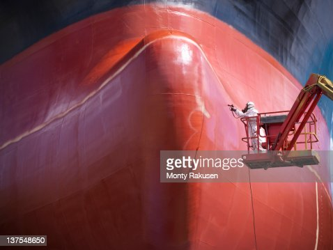 Spray painting underside of ship in dry dock