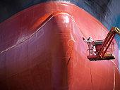 Spray painting underside of ship in dry dock