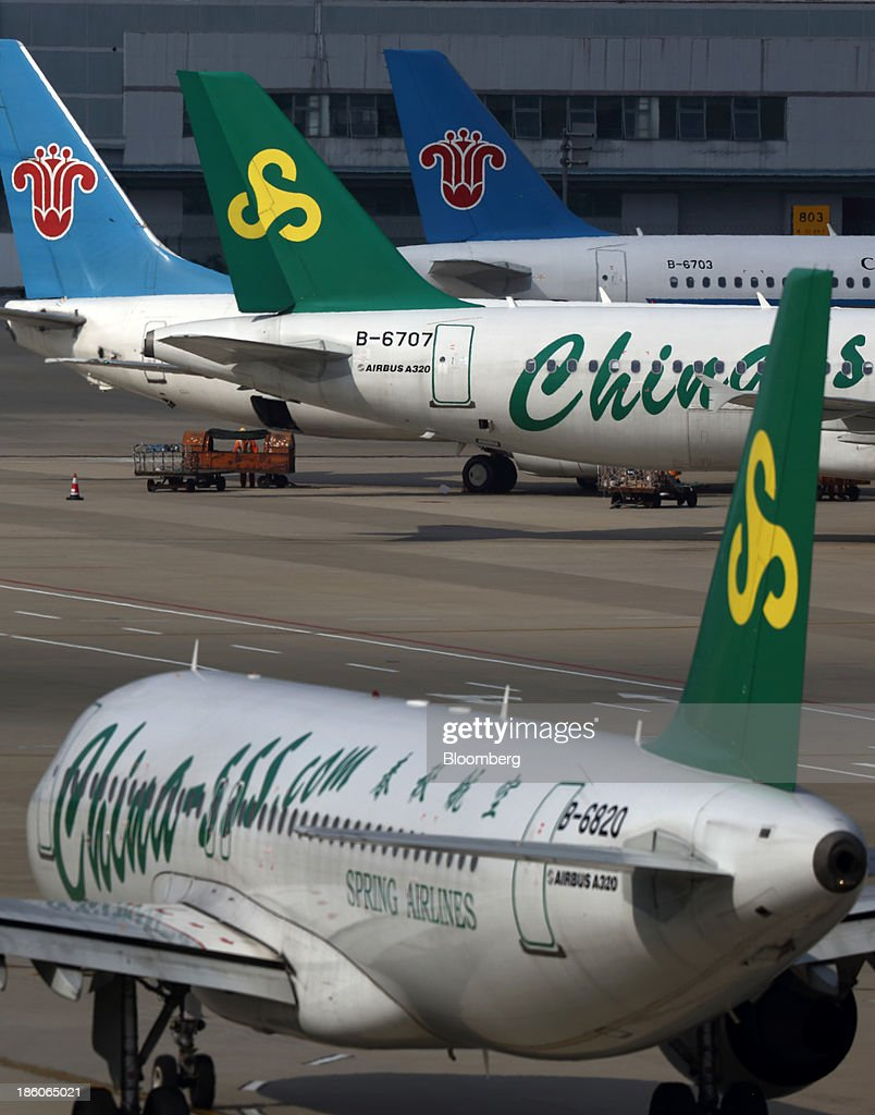 Spring Airlines Co. and China Southern Airlines Co. aircraft stand on the tarmac at Shanghai Pudong International Airport in Shanghai, China, on Saturday, Oct. 26, 2013. Airline profits worldwide in 2013 will be 7.9 percent smaller than estimated at $11.7 billion amid sluggish travel demand and rising oil prices tied to the Syria crisis, the International Air Transport Association said last month. Photographer: Tomohiro Ohsumi/Bloomberg via Getty Images