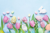 Spring background with flowers, bunny, colorful eggs and feathers on blue table top view. Happy Easter card. Copy space for text.