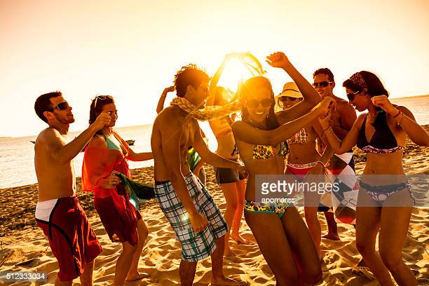 Spring break backlit group of young people dancing on beach