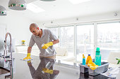 Shot of a young mixed race man cleaning a kitchen top. The kitchen is open planned and spacious.