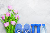 Spring flatlay sports composition with blue sneakers, dumbbells, bottle