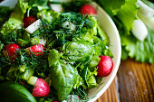 Spring salad from early vegetables, lettuce leaves, radishes and herbs in a white bowl