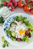 Spring vegetables salad with poached egg and yoghurt sauce
