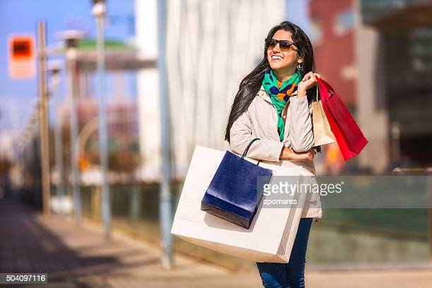 Springtime shopping. Hispanic young woman walking with bags on street