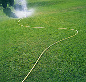 Sprinkler on slope spraying water over grass