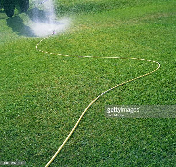Sprinkler on slope spraying water over grass
