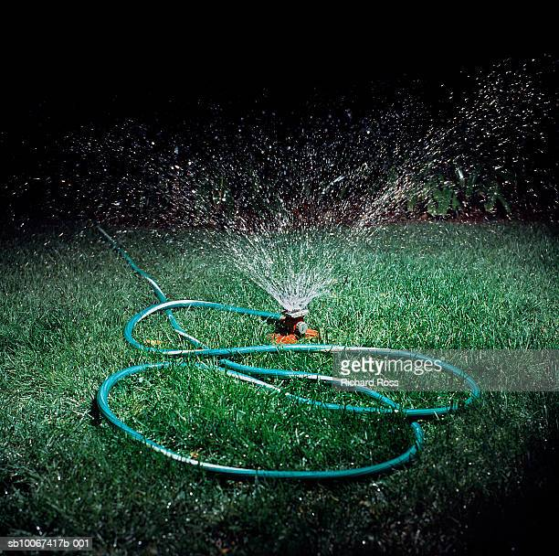 Sprinkler spitting water on lawn at night