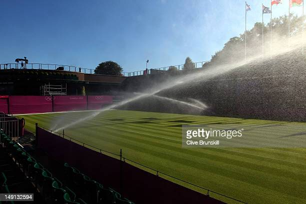 Sprinklers spray water across the grass on an outside court during previews ahead of the 2012 London Olympic Games at the All England Lawn Tennis and...