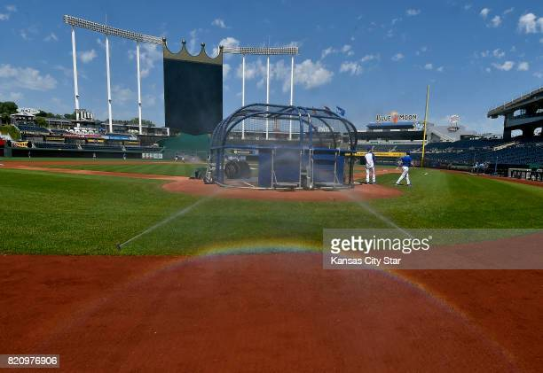 Sprinklers water around the edge of the infield as the Kansas City Royals take optional batting practice in the heat before a game against the...