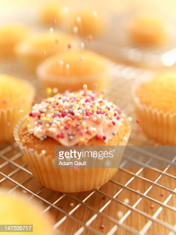 Sprinkles falling on frosted cupcake : Stock Photo