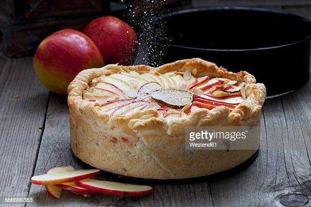 Sprinkling baked apple pie with icing sugar