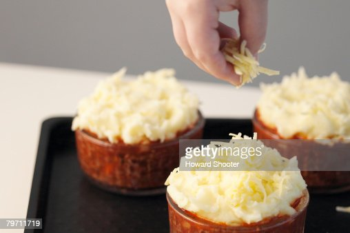 Sprinkling cheese on to uncooked pies, close up