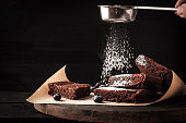 Sprinkling chocolate brownie with icing sugar on the wooden board horizontal