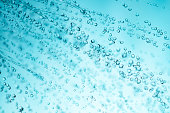 sprinkling water from shower head, closeup, blue toned photo