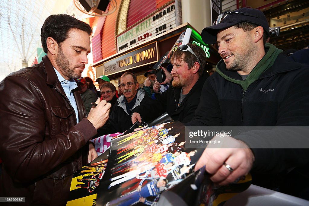 Sprint Cup Series Champion Jimmie Johnson signs autographs at a fanfest hosted by Las Vegas Motor Speedway on the Third Street Stage at the Fremont Street Experience on December 4, 2013 in Las Vegas, Nevada.