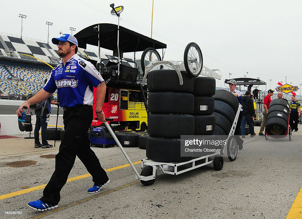 Sprint Cup Series crew members bring tires to their pit boxes along pit road at Daytona International Speedway in Daytona Beach, Florida, Sunday, February 24, 2013.