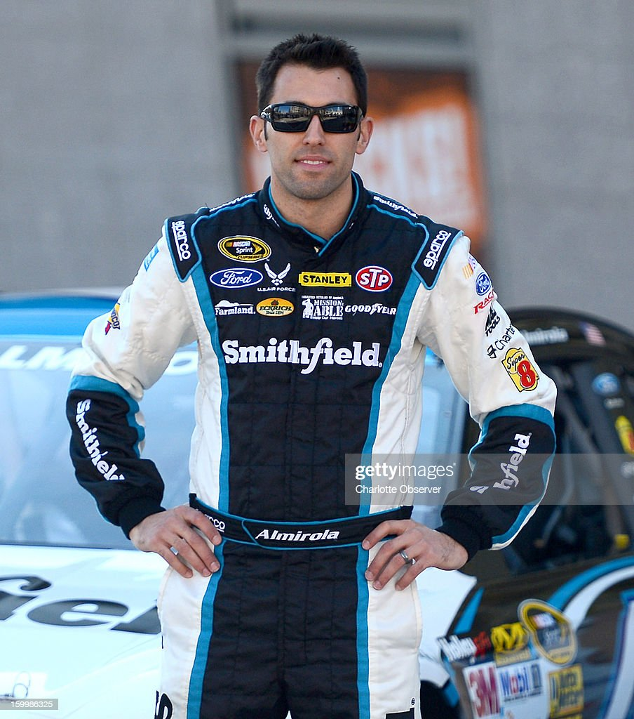 Sprint Cup Series driver Aric Almirola poses next to his car in the NASCAR Hall of Fame Plaza following the Ford Racing parade through uptown Charlotte, North Carolina, Thursday, January 24, 2013. The parade featured all of the Ford drivers in the Sprint Cup Series for the 2013 season.