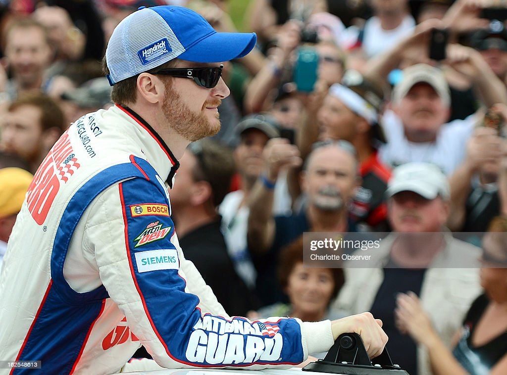 Sprint Cup Series driver Dale Earnhardt Jr. stands in the bed of a pickup as he is driven around the track prior to the Daytona 500 at Daytona International Speedway in Daytona Beach, Florida, Sunday, February 24, 2013.
