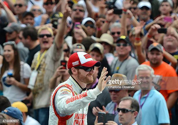 Sprint Cup Series driver Dale Earnhardt Jr waves to fans after being introduced during driver introductions for the Daytona 500 at Daytona...