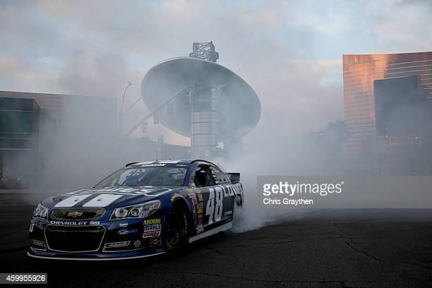 Sprint Cup Series driver Jimmie Johnson does a burnout in his car during the NASCAR Victory Lap on the Las Vegas Strip on December 4 2014 in Las...