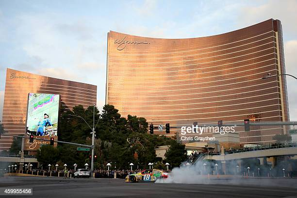 Sprint Cup Series driver Kyle Busch does a burnout in his car during the NASCAR Victory Lap on the Las Vegas Strip on December 4 2014 in Las Vegas...