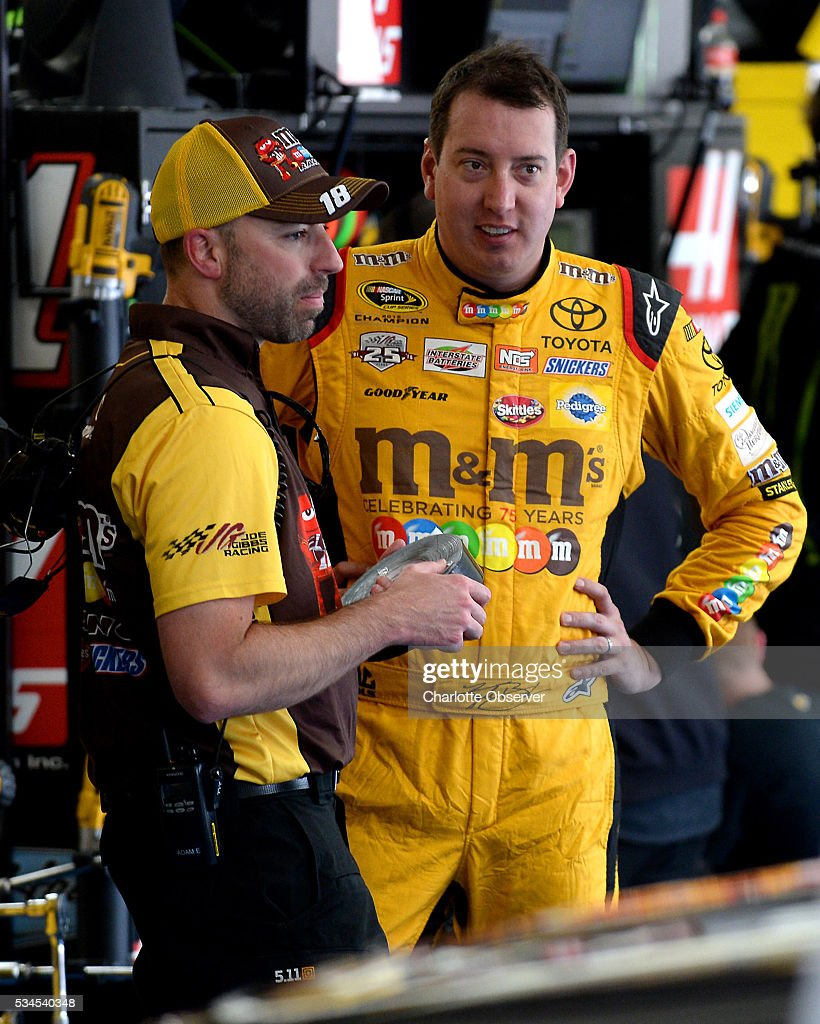 Sprint Cup Series driver Kyle Busch, right, relaxes in the garage as members of his team make adjustments to the car during practice at Charlotte Motor Speedway in Concord, N.C., on Thursday, May 26, 2016.