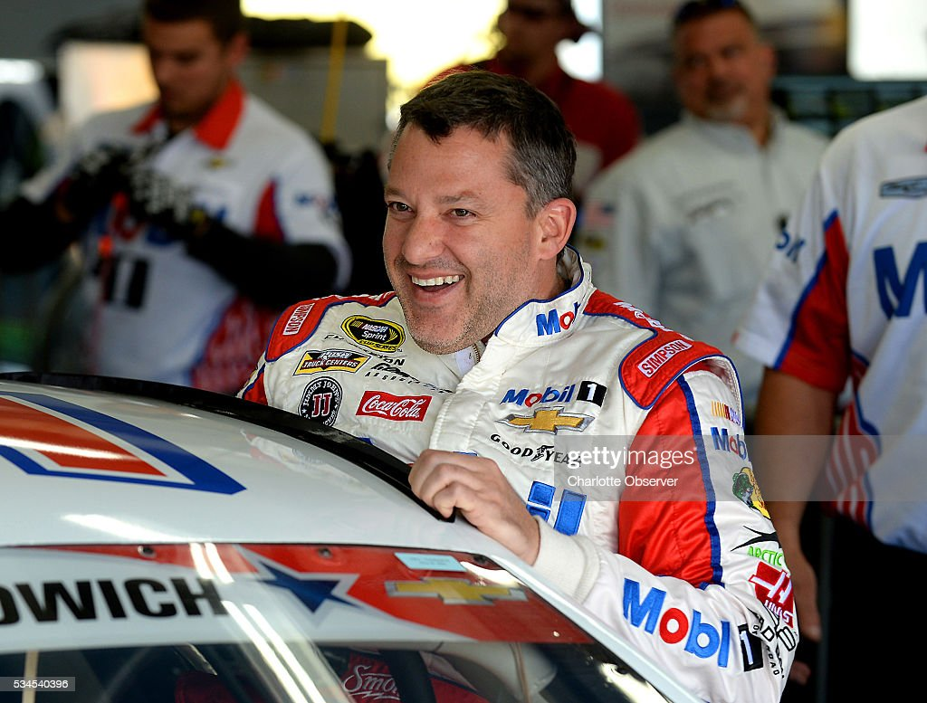 Sprint Cup Series driver Tony Stewart laughs with members of his team as he climbs into his car for practice at Charlotte Motor Speedway in Concord, N.C., on Thursday, May 26, 2016.