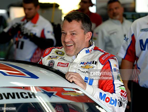 Sprint Cup Series driver Tony Stewart laughs with members of his team as he climbs into his car for practice at Charlotte Motor Speedway in Concord...