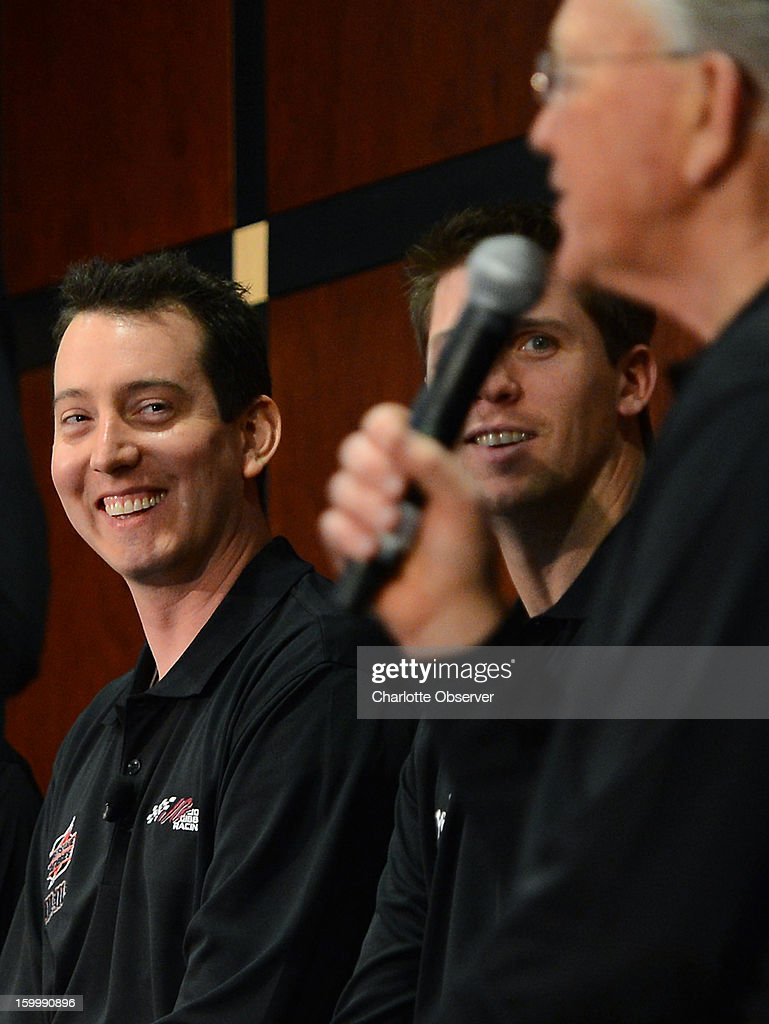 Sprint Cup Series drivers Kyle Busch, left, and Denny Hamlin listen to team owner Joe Gibbs, as he answers a question during the Sprint NASCAR Media Tour on Thursday, January 24, 2013, at the NASCAR Hall of Fame in Charlotte, North Carolina.