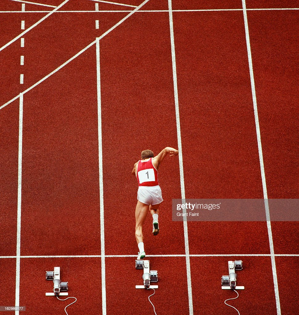 Sprint runner practising starts on a racing track : Stock Photo