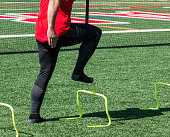 A high school track sprinter is in a-position while stepping over yellow mini banana hurdles on a green turf field during practice.