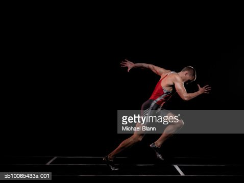 Sprinter running through finish line, studio shot, side view : Stock Photo