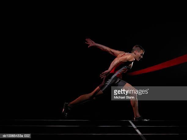 Sprinter running through finish line, studio shot, side view