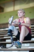 Sprinter sitting with prosthetic leg on
