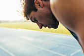 Closeup of a sprinter standing on a running track. Tired athlete relaxing after a run standing on the track.