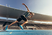Runner using starting block to start his run on running track in a stadium. Athlete starting his sprint on an all-weather running track.