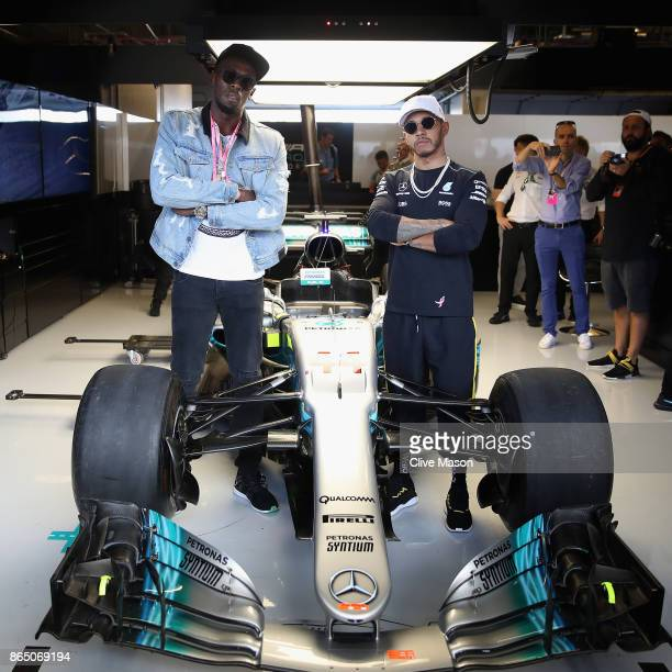 Sprinting legend Usain Bolt poses for a photo with Lewis Hamilton of Great Britain and Mercedes GP in the Mercedes F1 garage before the United States...