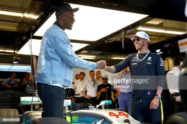 Sprinting legend Usain Bolt shakes hands with Lewis Hamilton of Great Britain and Mercedes GP in the Mercedes F1 garage before the United States...