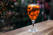 Aperol spritz cocktail in glass on wooden table on dark background in cafe.