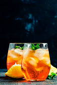 Spritz cocktail with ice, black background, selective focus